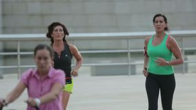 Two athletic women in sportswear running in public. Healthy active lifestyle. Stock footage stock video