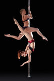 Two athletic young girls dancing on pilon Stock Image