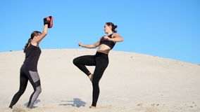 Two athletic, young women in black fitness suits are engaged in a pair, fulfill kicks, train to fight, on deserted beach. Two athletic, young women in black stock footage