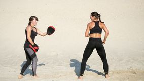 Two athletic, young women in black fitness suits are engaged in a pair, work out kicks, on a deserted beach, against a
