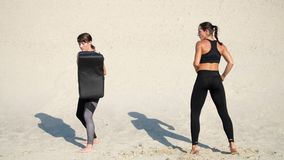 Two athletic, young women in black fitness suits are engaged in a pair, work out kicks, on a deserted beach, against a stock footage