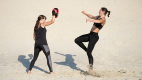 Two athletic, young women in black fitness suits are engaged in a pair, work out kicks, on a deserted beach, against a. Blue sky, in the summer, under a hot sun stock video footage