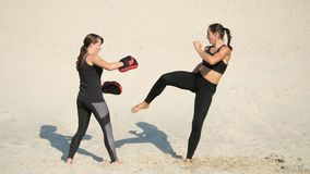 Two athletic, young women in black fitness suits are engaged in a pair, work out kicks, on a deserted beach, against a. Blue sky, in the summer, under a hot sun stock video