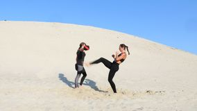 Two athletic, young women in black fitness suits are engaged in a pair, work out kicks, train, perform squats and kick. Ups, on deserted beach, in summer, under stock footage
