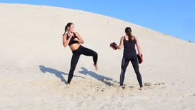 Two athletic, young women in black fitness suits are engaged in a pair, work out kicks, train, perform squats and kick. Ups, on deserted beach, in summer, under stock video