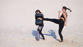 Two athletic, young women in black fitness suits are engaged in a pair, work out kicks, train, perform squats and kick. Ups, on deserted beach, in summer, under stock video footage