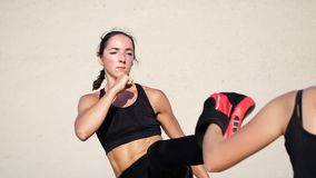 Two athletic, young women in black fitness suits are engaged in a pair, work out kicks, train to fight, on deserted. Beach, against a blue sky, in summer, under stock video footage