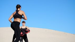 Two athletic, young women in black fitness suits are engaged in a pair, work out kicks, train to fight, on deserted. Beach, against a blue sky, in summer, under stock footage