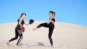 Two athletic, young women in black fitness suits are engaged in a pair, work out kicks, train to fight, on deserted. Beach, against a blue sky, in summer, under stock video
