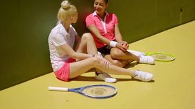 Two athletic young women tennis players. Two attractive stylish athletic young women tennis players relaxing together on the ground chatting as they wait to play stock footage