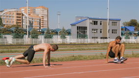 Two athlets prepare for training. Two caucasian male athlets preparing for training at the stadium. Two topless sportsmen warming up in face to ground position stock footage