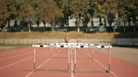 Two athlets run on short distance with hurdles at the stadium stock footage