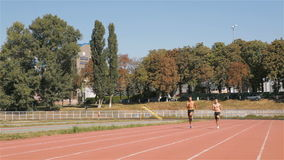 Two athlets run at the stadium. Two male athlets running by the runway at the stadium. Young sportsmen jogging before sprint. Two topless man running one near stock video