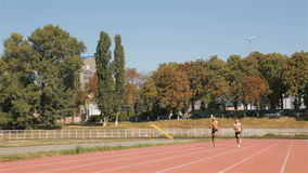 Two athlets sprinting at the stadium. Two topless athlets sprinting at the stadium. Young sportsmen beginning to run from standing start. Caucasian man from the stock footage