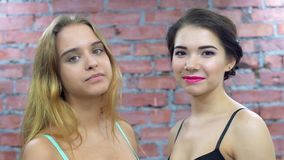 Two atrractive young girls in bra smiles on camera. Posing. Casting. Make up. Brick wall on background stock footage