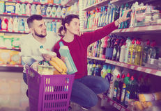 Two attentive adult people in good spirits selecting detergents. оn the shelves in the store Stock Photography