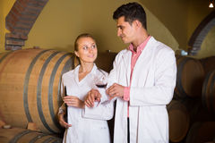 Two attentive wine house workers checking quality of product. In cellar Stock Photos