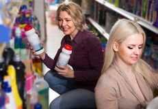 Two attentive women choosing some detergents. In the shop Stock Images