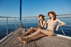 Two attractive adult woman on yacht, sailing in sea and sunbathing on bow of boat, feeling relaxed and pleased. Hot royalty free stock images