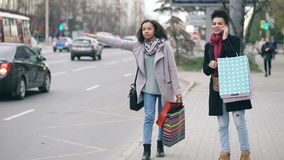 Two attractive african american women with shopping bags calling for taxi cab while coming back from mall sales. Two attractive african american women with stock footage