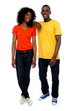 Two attractive african friends posing in style. As guy rests his hands over his girlfriends shoulders Stock Photography