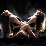 Two attractive beautiful show play dancing performers young women seductive girl friends in a bodysuit sitting and looking up stock photo