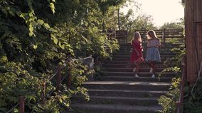Two attractive beautiful young blond women blow bubbles in the park and are happy on sunset. Girlfriends in park on the steps. In Odessa stock footage