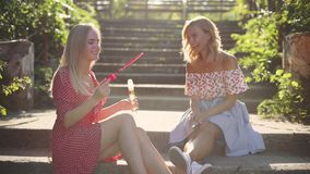 Two attractive beautiful young blond women blow bubbles in the park and are happy on sunset. Girlfriends in park on the steps. In Odessa stock video footage