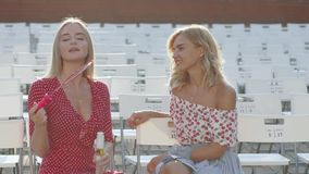 Two attractive beautiful young blond women blow bubbles in the park and are happy on sunset. Girlfriends in park. Slow motion. In Odessa stock footage