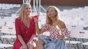 Two attractive beautiful young blond women blow bubbles in the park and are happy on sunset. Girlfriends in park. Slow motion. In Odessa stock video