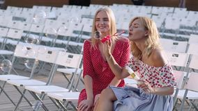Two attractive beautiful young blond women blow bubbles in the park and are happy on sunset. Girlfriends in park. Slow motion. In Odessa stock video footage