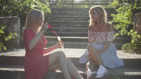 Two attractive beautiful young blond women blow bubbles in the park and are happy on sunset. Girlfriends in park on the steps. In Odessa stock video