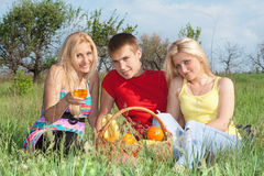 Two attractive blonde and young man Stock Images