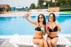 Two attractive brunette women wearing bikini posing near the swimming pool, making selfie photo. Summer time. Two attractive brunette women wearing bikini posing stock photography
