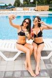 Two attractive brunette women wearing bikini posing near the swimming pool, making selfie photo. Summer time. Two attractive brunette women wearing bikini posing royalty free stock image