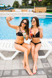 Two attractive brunette women wearing bikini posing near the swimming pool, making selfie photo. Summer time Royalty Free Stock Photography