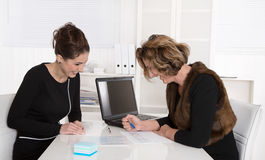 Two attractive business colleagues working together at desk at o Stock Photo