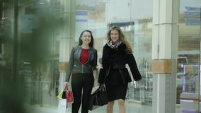 Two attractive business lady walk around the Mall after shopping. Filmed in the city of Togliatti in the shopping center Park house stock video