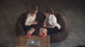 Two attractive business woman relaxing on a sofa and watching photo on the tablet. stock video
