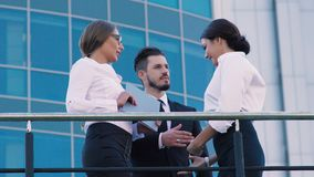 Two attractive business women meeting a business man outdoors. They greet each other and shake hands stock footage