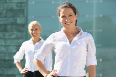 Two attractive business women posing outside. Two young attractive business women posing outside royalty free stock image