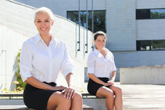 Two attractive business women sitting over street background Stock Photography