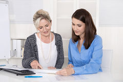 Two attractive businesswoman in meeting analyzing budget. Royalty Free Stock Image