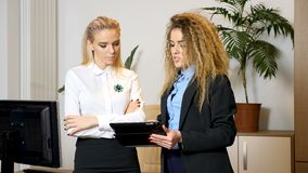 Two attractive businesswomen standing in the office and talking. One is showing and explaining something to the other pointing at the digital tablet that she stock video