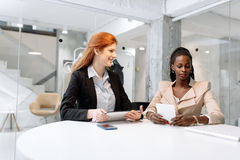 Two attractive businesswomen using technology Royalty Free Stock Photo