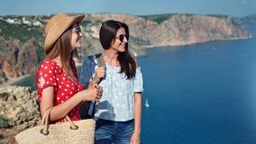 Two attractive casual travel girl admiring beautiful seascape from top of mountain medium shot. Smiling female friend making gesture showing amazing nature stock video