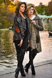 Two attractive Caucasian women posing against the lake in the park. Stock Photography