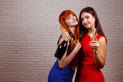 Two attractive cheerful girls dancing, having fun and drinking c royalty free stock photo