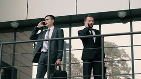 Two attractive and confident businessman holding their briefcases talking on cell phones. Two attractive and confident businessmen stand at the entrance of the stock video