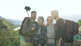 Two attractive couple posing on the smart phone camera in the mountain. stock video footage